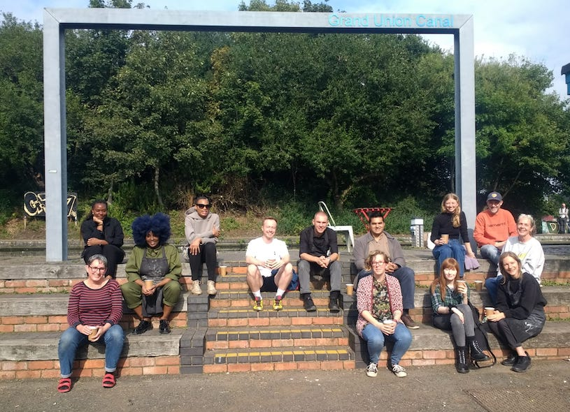 Thirteen smiling people sitting on brick steps by the canal